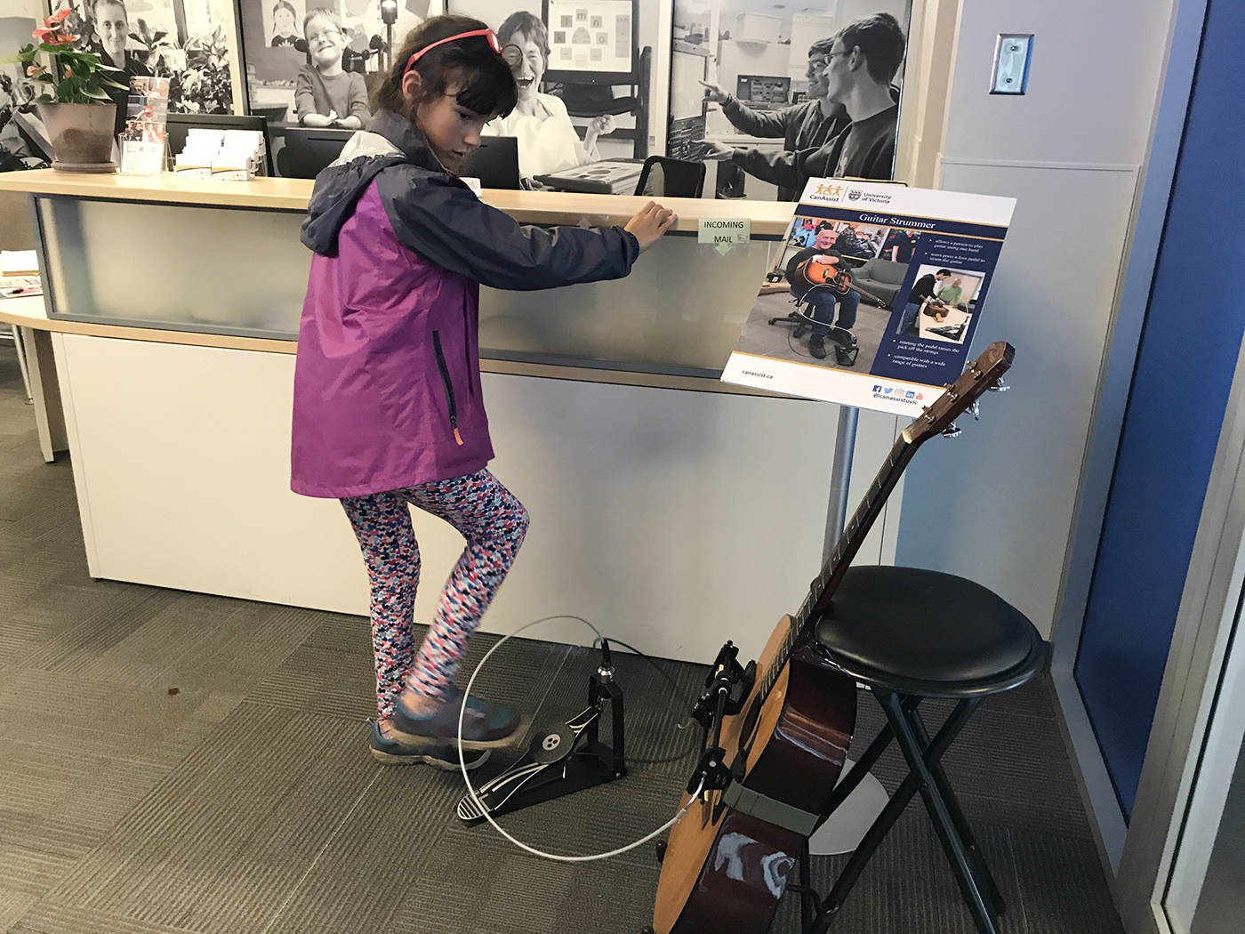 Asha Horter tries out the guitar strummer, played through a foot pedal, at CanAssist at the University of Victoria. (Keri Coles/News staff)